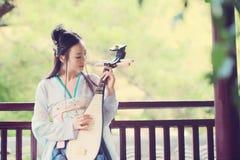 A mulher chinesa no vestido tradicional de Hanfu, joga o instrumento tradicional do pipa imagens de stock royalty free
