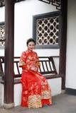 Mulher chinesa nova, bonita e elegante que veste o vestido vermelho de seda de uma noiva chinesa típica, assento decorado no banc imagens de stock royalty free