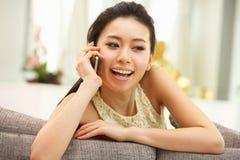 Mulher chinesa nova que usa o telefone móvel em casa Fotografia de Stock Royalty Free