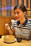 Mulher chinesa que come a bolinha de massa cozinhada no restaurante fotografia de stock