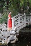 Mulher chinesa que veste o vestido vermelho de seda de uma noiva chinesa típica, decorado com phoenix dourado e para arrastar na  fotos de stock