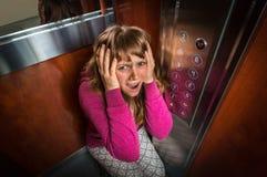 Mulher chocada com claustrofobia no elevador movente fotografia de stock