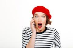 Mulher chocada jovens que fala pelo telefone celular Imagem de Stock