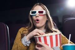 mulher chocada nos vidros 3d com a cesta grande do filme de observação da pipoca Fotografia de Stock
