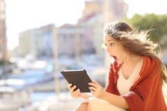 Mulher chocada que olha o índice em linha em uma tabuleta fotografia de stock