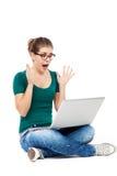 Mulher chocada que olha o portátil Fotografia de Stock Royalty Free