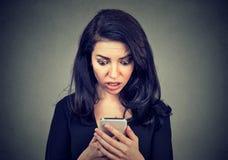 A mulher chocada que olha o telefone celular preocupou-se com notícia que má da mensagem recebeu Fotografia de Stock