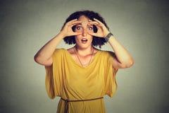 A mulher chocado, espreitando a vista através dos dedos gosta da pesquisa dos binóculos Imagens de Stock