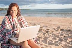 Mulher coberta com o portátil de utilização geral na praia Imagens de Stock