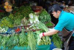 A mulher coloca a grama para a venda em um mercado vegetal Imagens de Stock