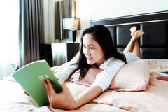 A mulher coloca na cama que lê o livro vazio imagens de stock