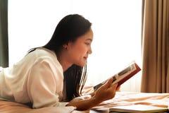 A mulher coloca na cama que lê o livro vazio foto de stock royalty free