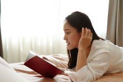 A mulher coloca na cama que lê o livro vazio foto de stock