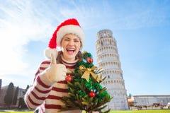 Mulher com a árvore de Natal que mostra os polegares acima da excursão de inclinação próxima Fotografia de Stock Royalty Free
