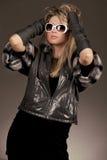 Mulher com óculos de sol e o revestimento de couro Imagens de Stock