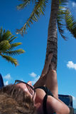 Mulher com óculos de sol que toma sol abaixo da palmeira Fotografia de Stock Royalty Free