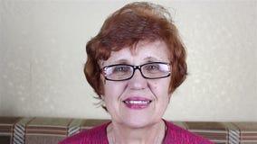 Mulher com óculos idosa bonita que sorri e que olha a câmera filme