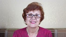 Mulher com óculos idosa bonita que sorri e que olha a câmera vídeos de arquivo