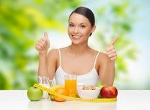 Mulher com alimento e fita métrica que mostra os polegares acima imagens de stock royalty free