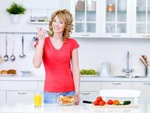 Mulher com alimento saudável na cozinha Fotografia de Stock Royalty Free