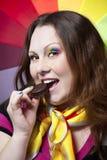 A mulher com arco-íris compo comer o bolinho Imagem de Stock