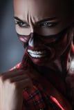 Mulher com arte da cara no tema do Dia das Bruxas que olha afastado Fotos de Stock Royalty Free