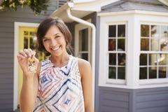 Mulher com as chaves que estão a casa nova exterior imagens de stock royalty free