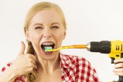 Mulher com as cintas que escovam os dentes com broca fotos de stock