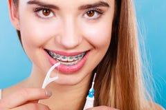 Mulher com as cintas que limpam os dentes com a escova de dentes Fotos de Stock