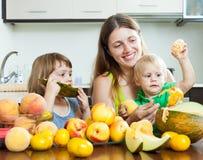 Mulher com as crianças que comem pêssegos Foto de Stock