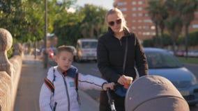 Mulher com as duas crianças que andam na cidade e no café bebendo vídeos de arquivo