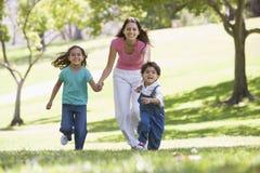 Mulher com as duas crianças novas que funcionam o sorriso Fotografia de Stock Royalty Free