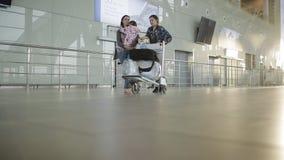 Mulher com as duas filhas que puxam o carro da mão da bagagem com os sacos ao longo do salão do aeroporto Passageiros na área de  video estoque