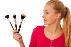 Mulher com as escovas dos cosméticos para a composição isoladas Fotografia de Stock