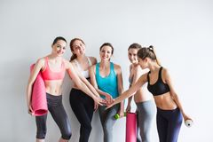 Mulher com as esteiras para a ioga no gym imagem de stock
