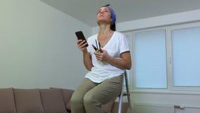 A mulher com as ferramentas do telefone e do trabalho senta-se na escada portátil video estoque