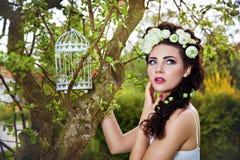 Mulher com as flores brancas no cabelo e no birdcage Imagem de Stock