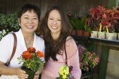 Mulher com as flores da terra arrendada da matriz Fotografia de Stock Royalty Free