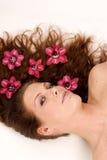 Mulher com as flores em seu cabelo Fotografia de Stock