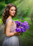 Mulher com as flores na floresta com ver dos raios de sol Foto de Stock Royalty Free