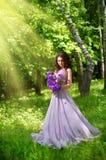 Mulher com as flores na floresta com ver dos raios de sol Imagens de Stock Royalty Free