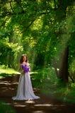 Mulher com as flores na floresta com ver dos raios de sol Fotografia de Stock