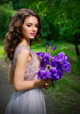 Mulher com as flores na floresta sem ver dos raios de sol Imagem de Stock