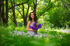 Mulher com as flores na floresta sem ver dos raios de sol Imagens de Stock