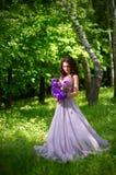 Mulher com as flores na floresta sem ver dos raios de sol Fotografia de Stock