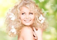 Mulher com as flores no cabelo e nas borboletas Fotos de Stock