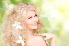 Mulher com as flores no cabelo e nas borboletas Foto de Stock