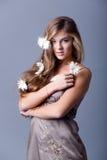 Mulher com as flores no cabelo no cinza Imagem de Stock Royalty Free