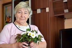 Mulher com as flores verdes de olho e brancas imagem de stock
