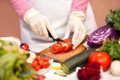 Mulher com as luvas que cortam o tomate com uma faca na cozinha Imagem de Stock Royalty Free